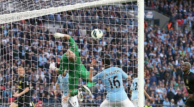 Wigan Athletic's Ben Watson (obscured) scores the winning goal past Manchester City goalkeeper Joe Hart during the FA Cup Final at Wembley Stadium