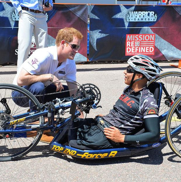 Prince Harry speaks to a competitor during the Warrior Games cycling event at the US Air Force academy base in Colorado Springs
