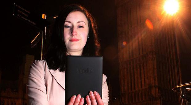 Gemma Tubbs reads her pre-ordered copy of the new Dan Brown novel Inferno on her Kindle Paperwhite device outside Parliament at midnight