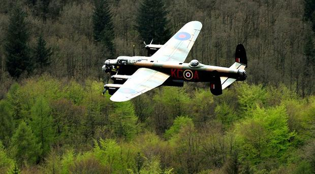 A Lancaster bomber during the Battle of Britain Memorial Flight performs a flypast over the Derwent Reservoir