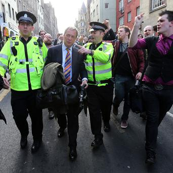 Ukip leader Nigel Farage is escorted by police officers as he leaves the Cannons Gait pub in Edinburgh amid a protest