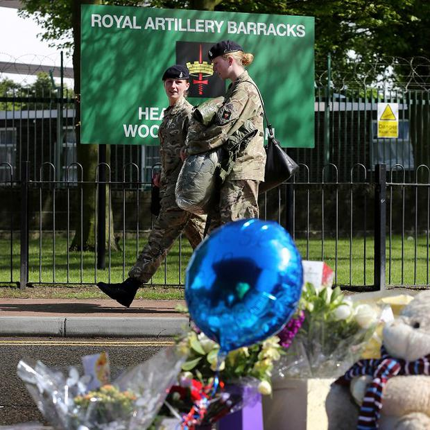 Soldiers walk past floral tributes outside the barracks in Woolwich (PA)