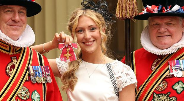 Cyclist Laura Trott with members of the Yeoman of the Guard, after receiving her OBE from the Prince of Wales at Buckingham Palace
