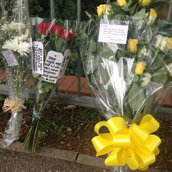 Floral tributes outside the gates of Hertswood Academy in Borehamwood