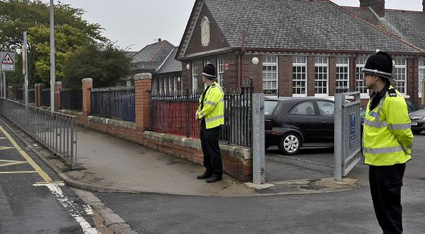 Police officers stand outside Rhoose Primary School where a car flipped over which left nine people injured, including five children