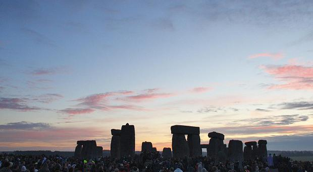 Dawn breaks at the World Heritage Site at Stonehenge as revellers gathered to watch the sunrise during the summer solstice