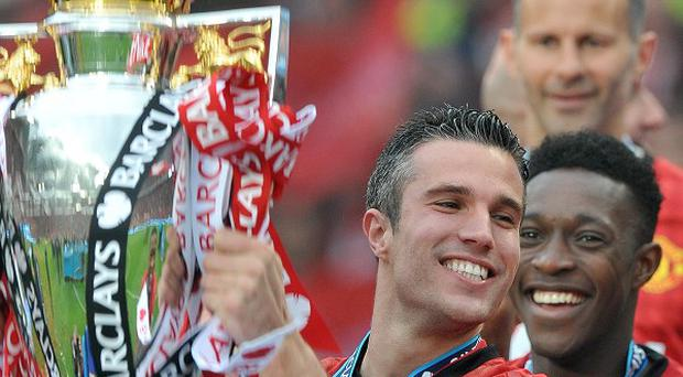 Manchester United's Robin Van Persie lifting the Barclays Premier League trophy