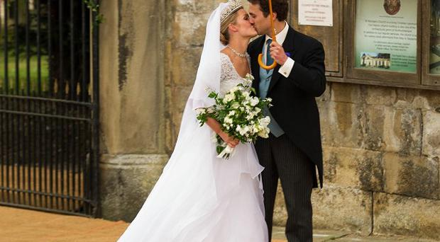 Lady Melissa Percy and Thomas van Straubenzee kiss after their wedding ceremony (PA)