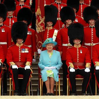 The Queen poses with Grenadier Guards after inspecting The Queen's Company at Buckingham Palace