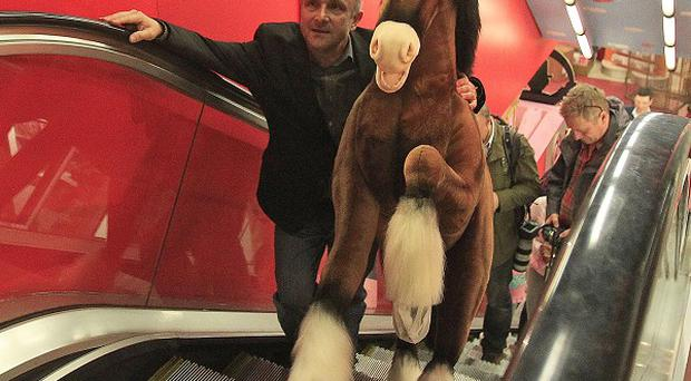 A Hamleys worker carries the Clydesdale Prancing Pony up an escalator as the London store previews its Christmas toy range (AP)