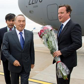 Prime Minister David Cameron, right, is greeted by President Nursultan Nazarbayev after landing in Kazahkstan