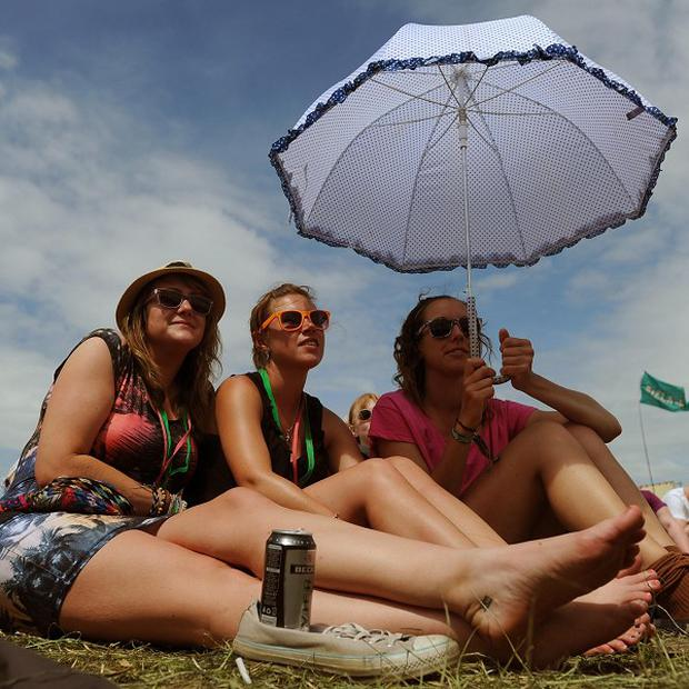 Festival-goers at Glastonbury enjoy the sunshine which looks set to continue through July