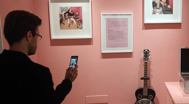 A man takes a picture of memorabilia on show at the Amy Winehouse exhibition at the Jewish Museum in London