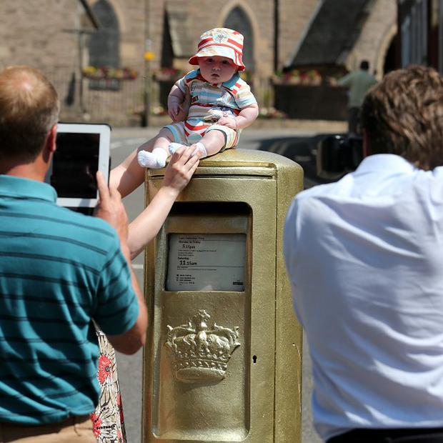 A baby has his picture taken on top of the gold post box in Dunblane High Street