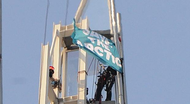A Greenpeace activist unveils a Save The Arctic flag on top of the Shard