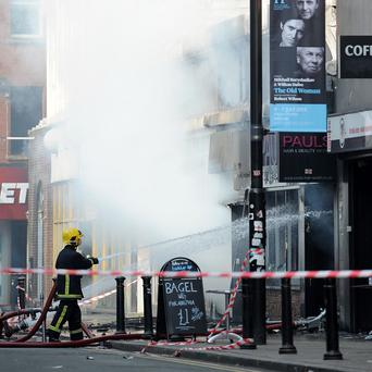 Firefighters at the scene of a fire at Paul's Hair World in Oldham Street, Manchester