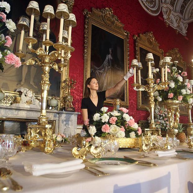 Exhibition curator Caroline de Guitaut, of the Royal Collection Trust, arranges the Coronation State Banquet display at Buckingham Palace