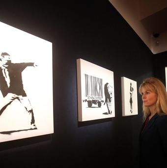 A Bonham's employee looks at Banksy pictures prior to a previous auction