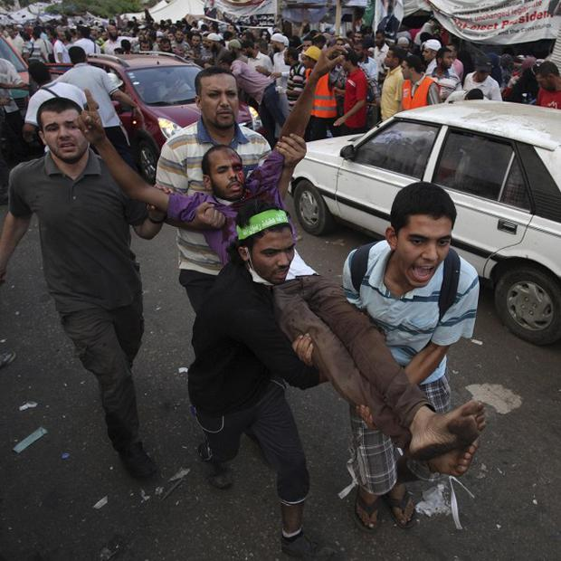 Supporters of Egypt's ousted President Mohammed Morsi carry an injured man to a field hospital (AP)