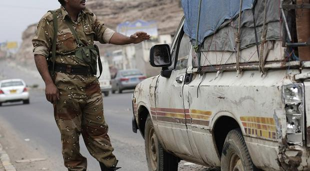 A Yemeni soldier stops a car at a checkpoint in a street leading to the US embassy in Sanaa (AP)