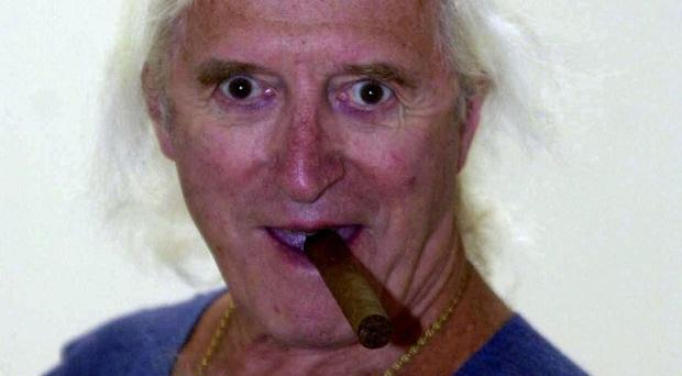 A group of people who dressed up as Jimmy Savile and schoolgirls at a community fancy dress competition have said sorry for causing offence