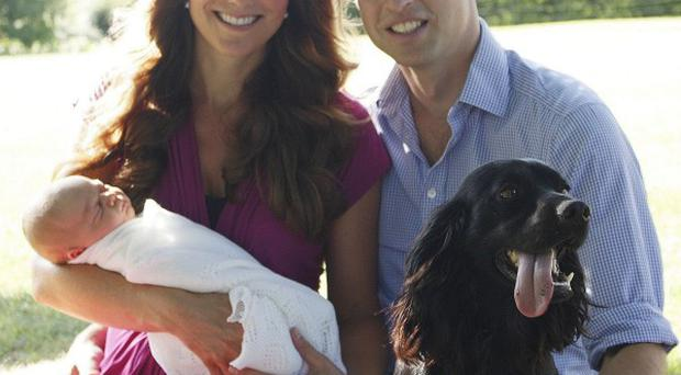 William, Kate and George sit on the grass with Middleton family pet, Tilly the retriever