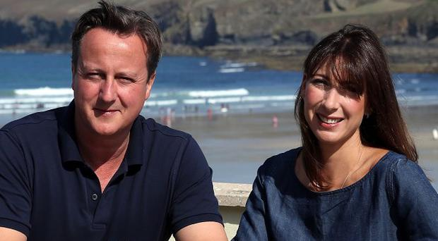 Prime Minister David Cameron and his wife Samantha sit on a bench outside a cafe overlooking the beach at Polzeath during their summer holiday (PA)