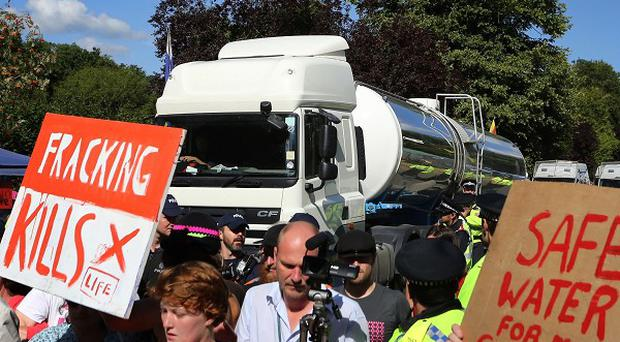 Environmental activists slow down a lorry heading to the Cuadrilla exploratory drilling site in Balcombe, West Sussex (PA)