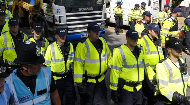 Police on foot escort a lorry as it arrives in Balcombe, West Sussex, where energy firm Caudrilla is performing exploratory drilling for oil