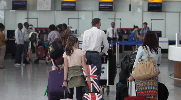 Passengers check in at Terminal 5 of Heathrow Airport ahead of the Bank Holiday weekend (PA)