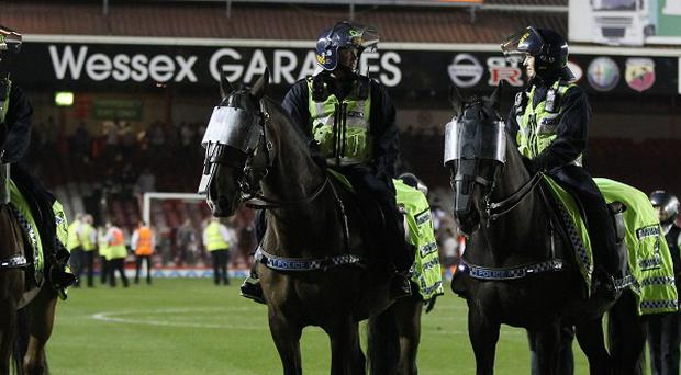 Riot police on horseback clear the pitch after Bristol City's derby match at Ashton Gate