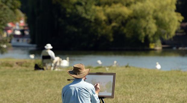 An artist paints on the banks of the River Thames under the shadow of Windsor Castle as the warm weather continues