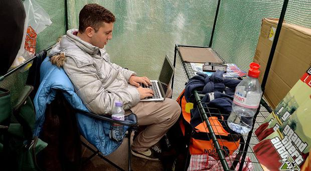 Gad Harari, 17, from London, sits undercover in a queue as he waits to buy the new iPhone