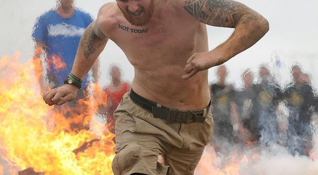 Double amputee James Simpson tackles the fire obstacle during the Spartan Super Race at West Midlands Water Ski Centre, Warwickshire