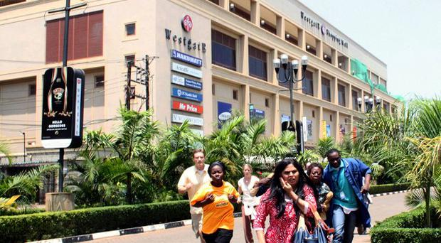 People run from the Westgate Mall in Nairobi after gunmen threw grenades and opened fire (AP)