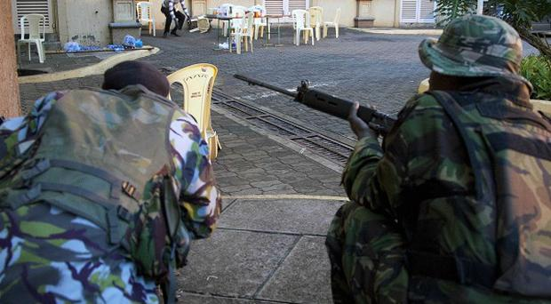 Security personnel take cover outside the Westgate shopping centre in Nairobi (AP/Sayyid Azim)