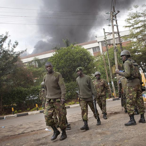 Kenyan security forces walk back from the Westgate Mall as black smoke billows above (AP)