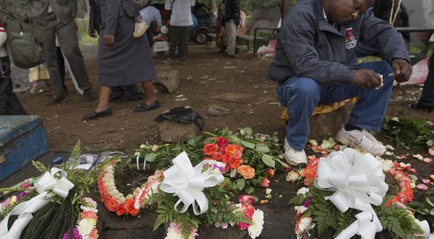 A street-seller makes floral wreaths outside the mortuary in Nairobi, Kenya (AP)