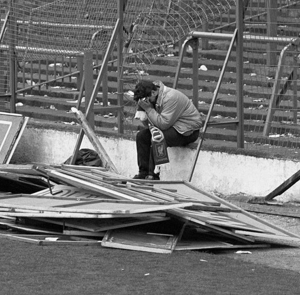 A Liverpool fan sits on the terraces at Hillsborough after the stadium disaster where 96 fans lost their lives.