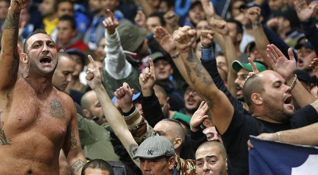 Napoli supporters gesture ahead of the Champions League Group F soccer match between Arsenal and Napoli at the Emirates Stadium in London, Tuesday, Oct. 1, 2013. (AP Photo/Matt Dunham)