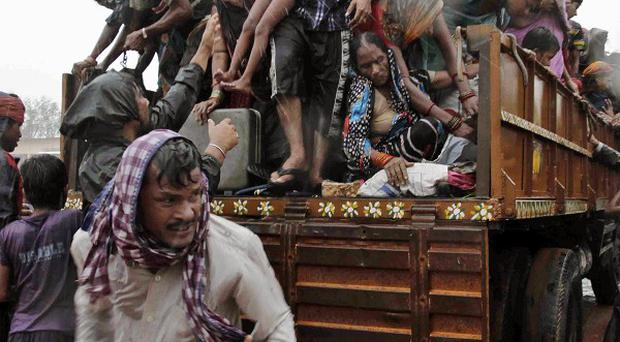 Evacuated Indian villagers get down from a truck at a relief camp as it rains near Berhampur, India (AP Photo/Bikas Das)
