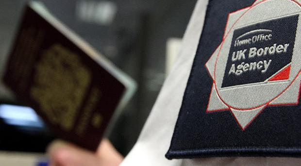 File photo dated 23/11/2009 of a UK Border Agency officer checking a passport as Britain is at risk of harbouring war criminals and terrorists due to poor decisions made by border officials, an influential group of MPs has warned.