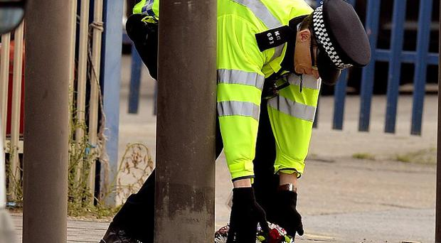 A police officer places flowers at the scene of Shammi Atwal's death in Barking, east London