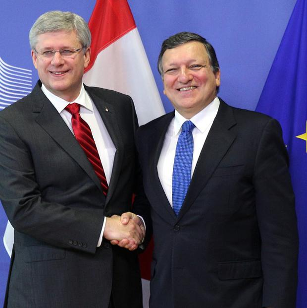 EC president Jose Manuel Barroso, right, shakes hands with Canadian prime minister Stephen Harper at the EC headquarters in Brussels after they signed off a free trade deal between Canada and the EU (AP)