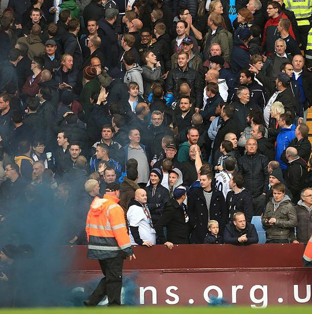 Police and stewards go into the away supporter's stand after a flare is thrown and hits assistant referee David Bryan