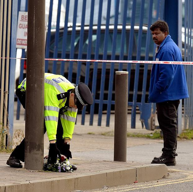 A Police Officer places flowers outside the Glen cash and carry warehouse in Barking, where Shammi Atwal was thrown under a passing lorry and killed