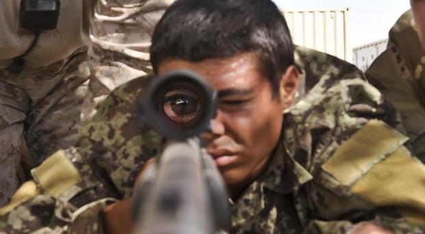 An Afghan National Army (ANA) soldier from 3 Brigade 209 Kandak looks through his rifle scope as he is trained on marksmanship skills in Helmand Province, by British and American soldiers.