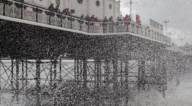Waves crash near Brighton Pier in East Sussex, as England and Wales face a battering from the worst storm in five years