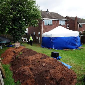 A man and woman have been arrested in a murder inquiry concerning remains found buried in a garden.