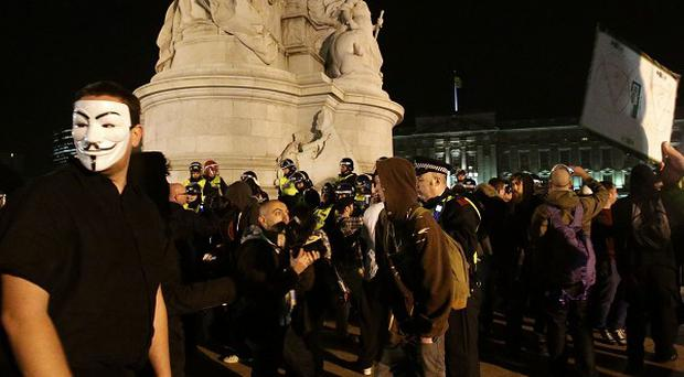 Protestors stand on the Queen Victoria Memorial outside Buckingham Palace, as they demonstrate during the Bonfire of Austerity protest in central London.